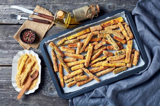 Varas de abobrinha crocantes empanadas com pão ralado de panko, queijo parmesão, especiarias em uma assadeira, lanche de verão saudável, visão horizontal de cima, camada plana