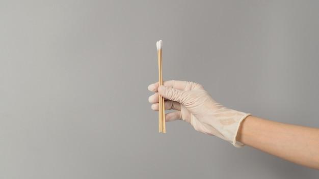 Varas de algodão para teste de cotonete em mãos com luvas médicas brancas sobre fundo cinza.