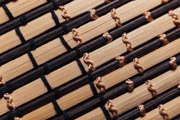 Varas de bambu são amarradas com fios brancos e bege. tapete de varas de madeira para o close-up da mesa.