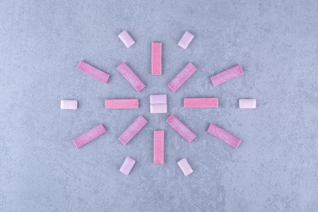 Varas de goma de mascar e comprimidos dispostos ordenadamente em um motivo na superfície de mármore