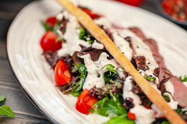 Varas de pão com uma salada de legumes e molho