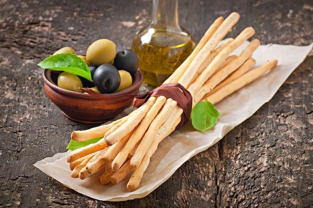 Varas de pão grissini com presunto, azeitonas, manjericão na velha de madeira