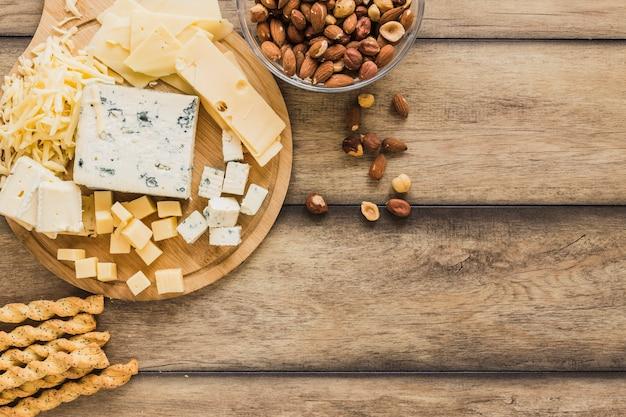 Varas de pão, queijo ralado e amêndoas tigelas na mesa de madeira