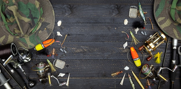 Varas de pesca e molinetes, equipamento de pesca no fundo de madeira preto