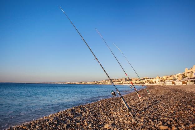 Varas de pesca em uma praia de calhau na promenade des anglais ao amanhecer, nice, frança