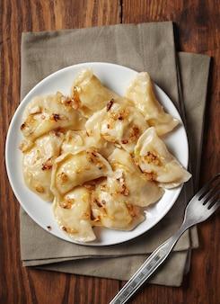 Vareniki caseiro (bolinhos) com batata e cebola em um prato.