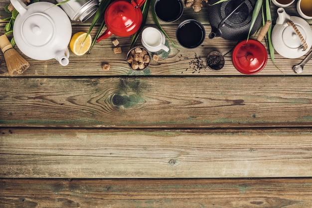 Vária composição de chá e bules, ervas secas, chá e chá matcha na mesa de madeira
