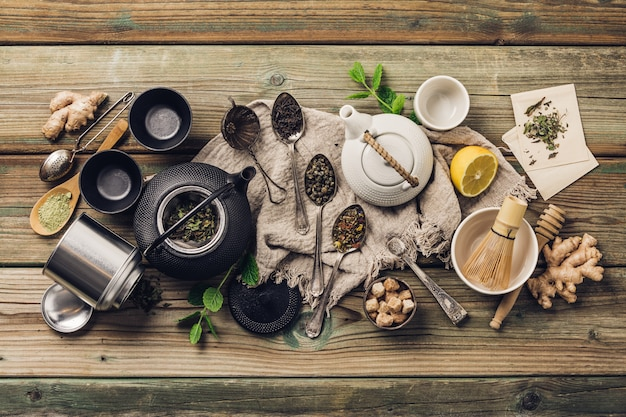 Vária composição de chá e bules, ervas secas, chá verde, preto e chá matcha na mesa de madeira