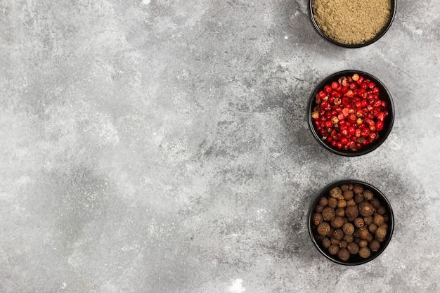 Vária pimenta em um fundo cinza. vista superior, copie o espaço. fundo de alimentos