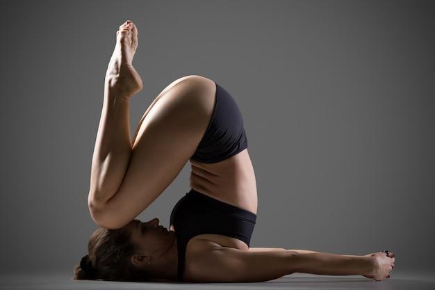 Variação da pose do yoga no joelho para a orelha