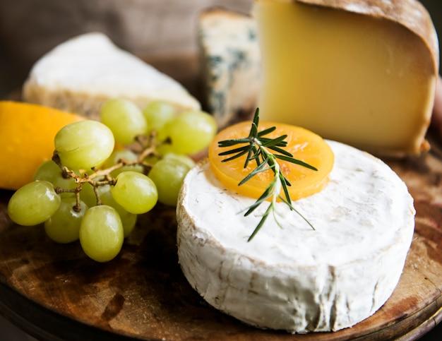 Variação de queijo e uvas verdes em uma ideia de receita de fotografia de comida de bandeja de madeira