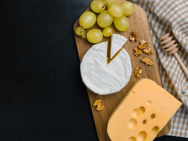Variação de queijo, nozes e uvas na tábua de madeira