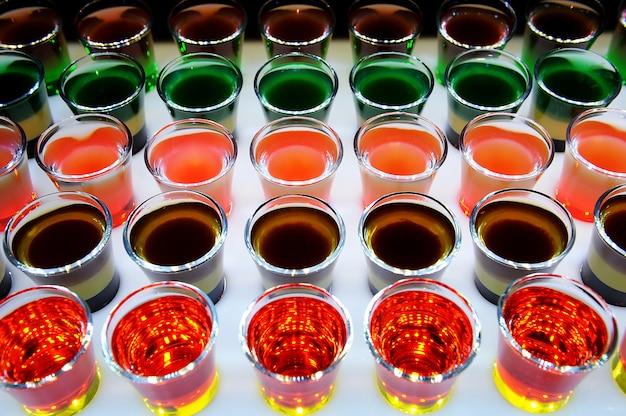 Variação de tiros alcoólicos duros servidos no balcão do bar.