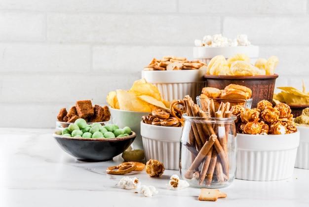 Variação diferentes biscoitos salgadinhos insalubres, pipoca salgada doce, tortilhas, nozes, palhas, bretsels