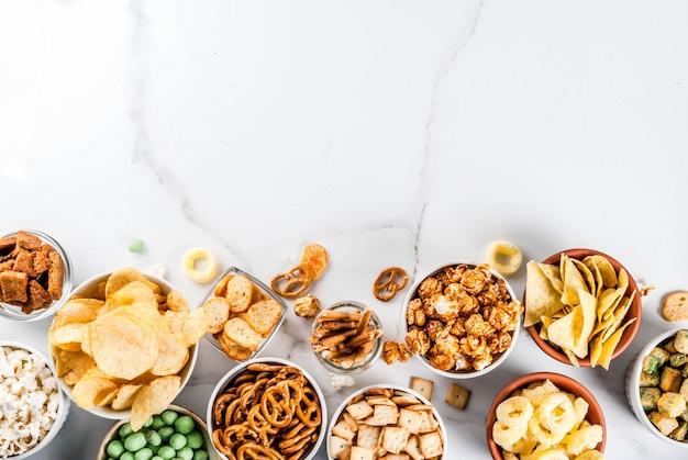 Variação diferentes biscoitos salgadinhos salgadinhos, pipoca salgada doce, tortilhas, nozes, palhas, bretsels, fundo de mármore branco cópia lanches salgados