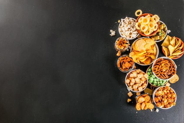 Variação diferentes petiscos insalubres bolachas doces salgados pipoca tortillas nozes palhas bretsels volta lousa