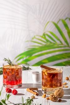 Variações de bebida refrescante espresso-tônica com diferentes frutas e xaropes na mesa de madeira sob o sol da manhã