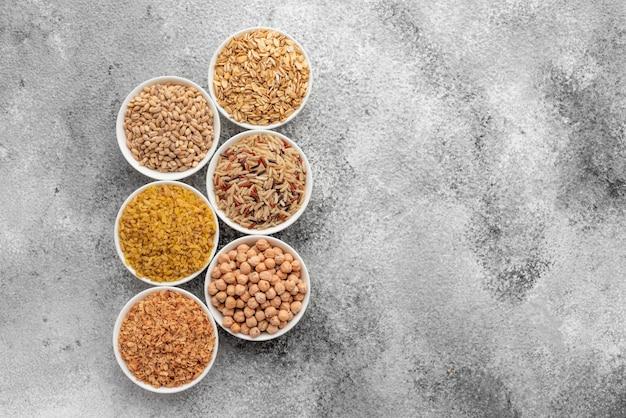 Variações de mingau e feijão em pires brancos sobre um fundo cinza concreto