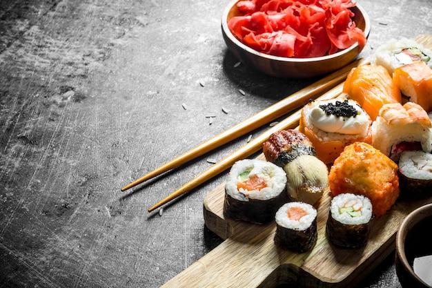 Variantes dos tipos de sushi, maki e rola em uma tábua com gengibre e molho de soja. na mesa rústica escura