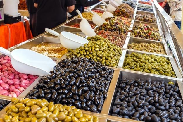 Várias azeitonas marinadas à venda em uma janela de mercado