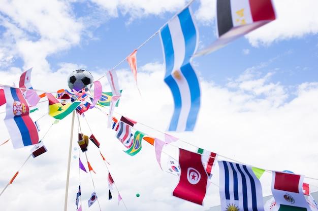 Várias bandeiras de país que tecem no vento e no céu azul em um fundo.