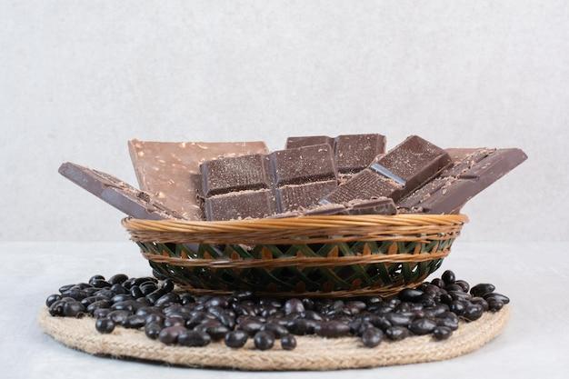 Várias barras de chocolate em cesto de madeira com bombons