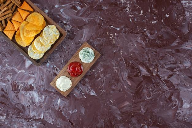 Várias batatas fritas na tábua de servir com molho, na mesa de mármore.