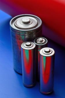 Várias baterias coloridas em um fundo azul-vermelho. fechar-se.