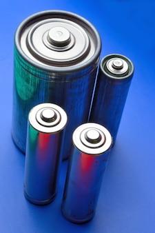 Várias baterias diferentes em um fundo azul. fechar-se.