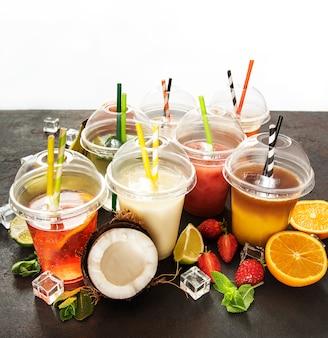 Várias bebidas geladas de verão e coquetéis em um fundo preto de concreto