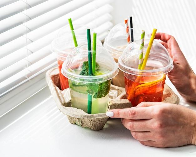 Várias bebidas geladas de verão e coquetéis em um suporte de papel nas mãos de mulheres