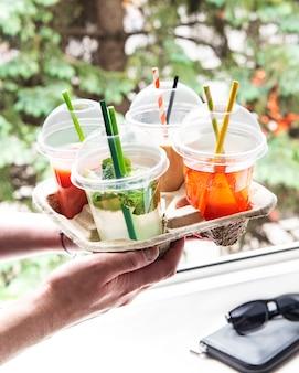 Várias bebidas geladas de verão e coquetéis em um suporte de papel nas mãos masculinas