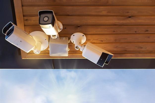 Várias câmeras de segurança sob o teto com edifícios e o fundo do céu
