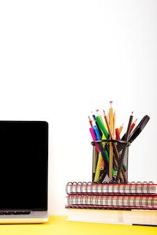Várias canetas e lápis no suporte sobre o caderno empilhados perto de laptop