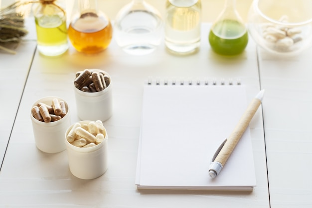 Várias cápsulas com suplementos dietéticos, ingredientes para a sua criação e um caderno com caneta.