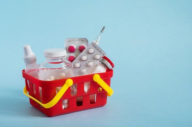 Várias cápsulas, comprimidos e medicamentos no carrinho de compras vermelho