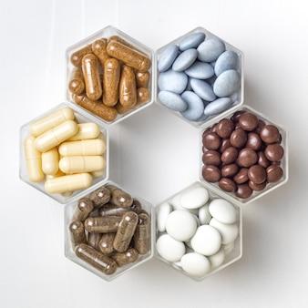 Várias cápsulas e comprimidos com suplementos dietéticos ou medicamentos em potes hexagonais têm a forma de um favo de mel