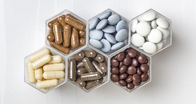 Várias cápsulas e comprimidos médicos em potes hexagonais em forma de favo de mel