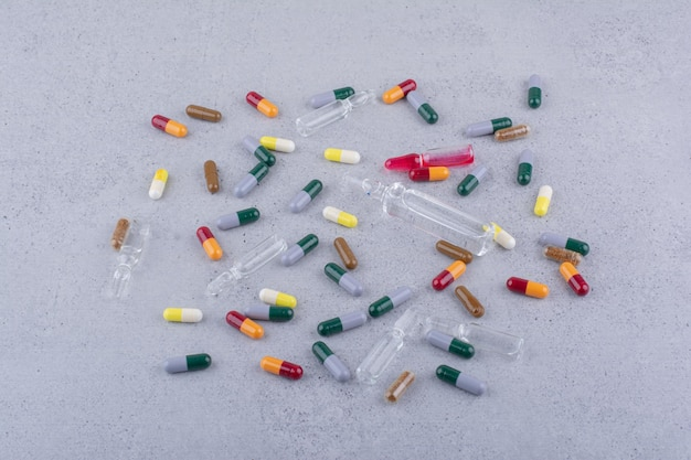Várias cápsulas farmacêuticas e ampolas na superfície de mármore. foto de alta qualidade