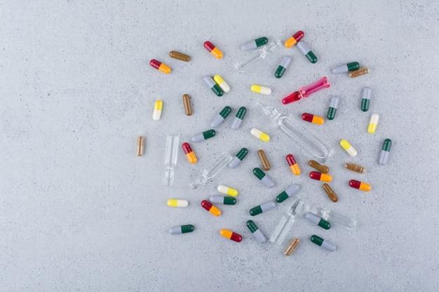 Várias cápsulas farmacêuticas e ampolas na superfície de mármore.