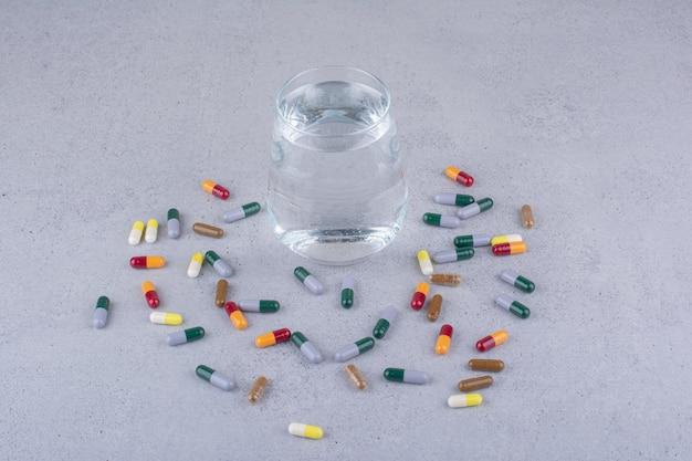 Várias cápsulas farmacêuticas e um copo de água. foto de alta qualidade
