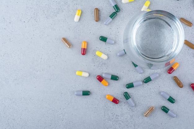 Várias cápsulas farmacêuticas e um copo de água.