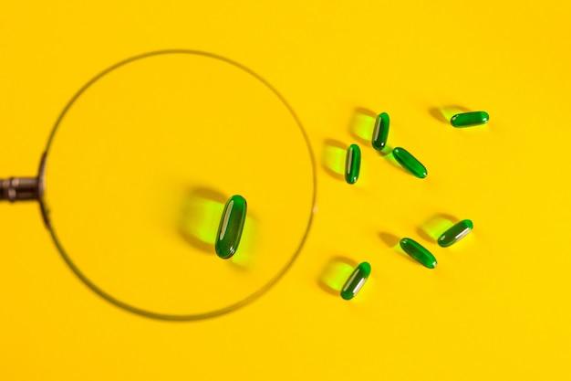 Várias cápsulas transparentes verdes dispostas em um amarelo sob uma lupa. saúde. a farmacologia.