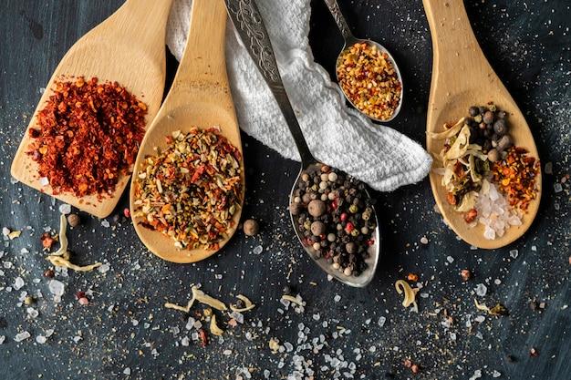 Várias colheres com mistura variaty de diferentes especiarias derramadas nas mesas