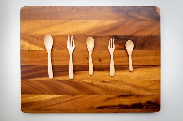 Várias colheres e garfos de madeira foram colocados em um pano de fundo de laca polida.