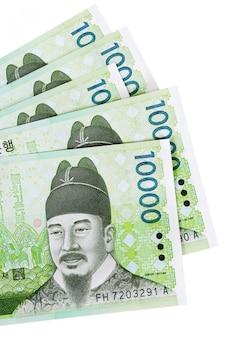 Várias contas de moeda coreana de 10.000 won totalmente isoladas contra branco