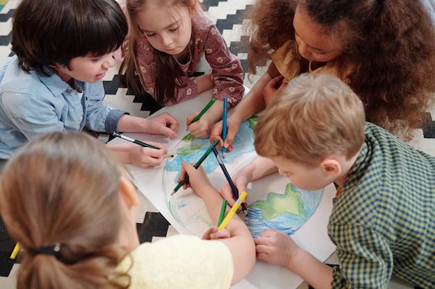 Várias crianças diligentes desenhando nosso planeta com giz de cera