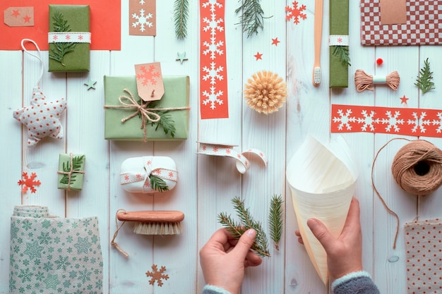 Várias decorações ecológicas de férias de inverno para natal ou ano novo, pacotes de papel ofício e presentes artesanais ou sem desperdício. apartamento leigos na madeira, mãos fazendo decorações artesanais com folhas verdes.