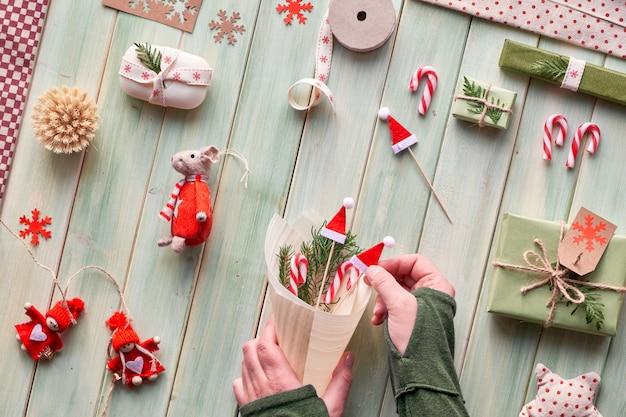 Várias decorações ecológicas de férias de inverno para natal ou ano novo, pacotes de papel para artesanato e presentes reutilizáveis ou com zero desperdícios. postura plana na madeira, mãos segurar decorações artesanais com folhas verdes.
