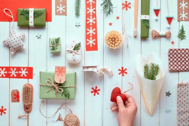 Várias decorações naturais de férias de inverno de natal ou ano novo, pacotes de papel ofício e presentes ecológicos zero resíduos amarrados com cordão e folhas verdes. apartamento leigos na madeira, mão segurando o coração de feltro.